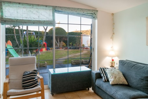 The living area offers a large window front with access to the terrace